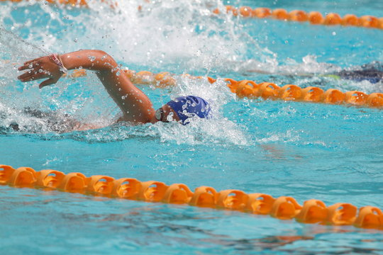 Young swimmer wearing blue cap practice freestyle stroke in a swimming pool for competition or race