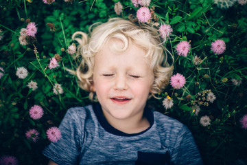 Boy with curly hair lay on grass and wild flowers