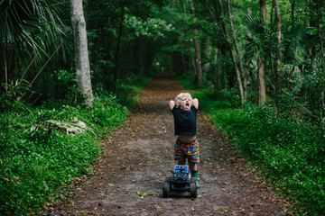 Small boy have a tantrum close to woodland