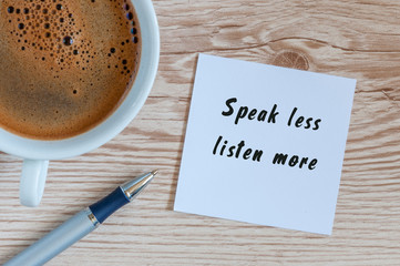 Speak Less Listen More phrase written on paper and cup of brasilian coffee at wooden background