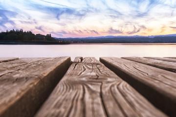 Panorama del Lago di Garda,Italia, con le assi di legno di un pontile in primo piano
