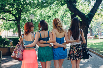 Four girl friends with their arms around each other