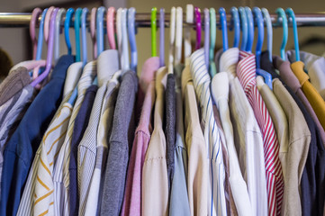 Abstract closeup shot, fabric texture of shirts with hangers on rack, selective focus