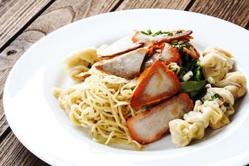 Egg noodles with red BBQ roast pork, dumpling, wontons and veget