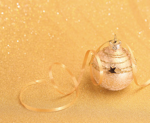 Christmas decorative ball on gold glitter background