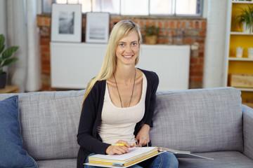 lächelnde frau sitzt auf dem sofa und lernt