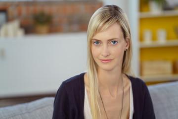 portrait einer jungen blonden frau in ihrer wohnung