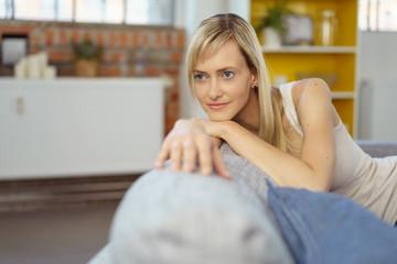 junge frau mit blonden haaren auf ihrem sofa