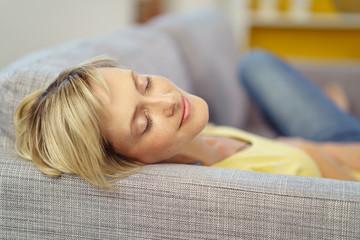 lächelnde frau liegt träumend auf dem sofa
