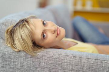 frau liegt auf dem sofa und schaut zurück
