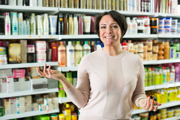 Brunette selecting bottle of shampoo