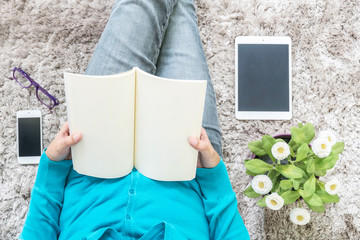 Closeup asian woman sitting on gray carpet at floor in house textured background for read a book in relax time with artificial plant , tablet , smart phone and eyeglasses , free time at house concept