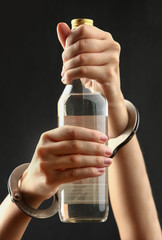 Bottle with alcohol drink in hands on a dark background. The concept of alcoholism
