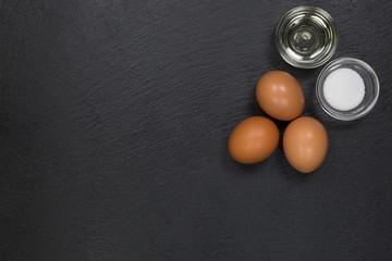 Drei braune Eier, eine Schale Öl und Salz auf einer Schieferplatte in der rechten oberen Ecke