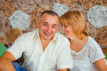 Adult blonde woman leans to her man's shoulder while they sit on