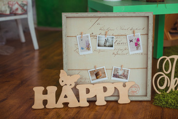 Wooden lettering Happy stands before the box with phographs
