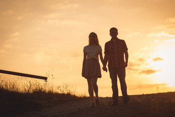 Golden sunset shines behind young couple holding their hands tog