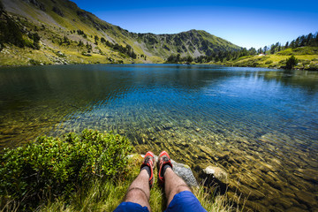 Lake and legs during mountain hiking at Pyrenean mountain