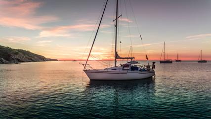 bateau à voile dans une crique au levé du soleil