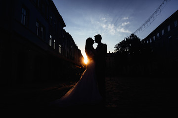 Silhouettes of wedding couple standing on the street in the rays