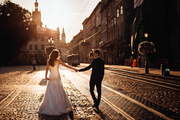 Bride and groom stretch their hands while walking along the tram