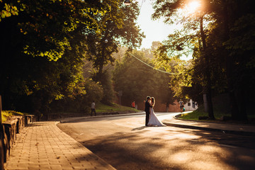 Evening sun illuminates the street where wedding couple kisses