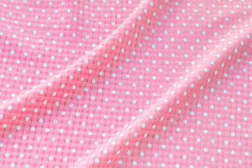 pink polka dot fabric ,Creased pink polka dot cloth material fragment as a background