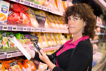 Woman comparing prices with her smartphone in supermarket