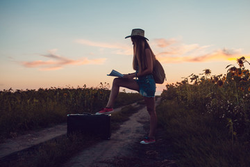Girl in cowboy hat sitting on a suitcase in a sunflower field. Sunset.