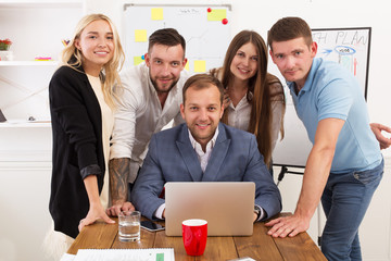 Happy business people team together near laptop in office