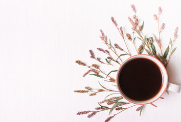 Cup of coffee with pink flowers, top view