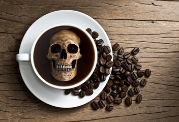 Still life photography : human skull soak in white coffee cup in harmful effect from Caffeine concept