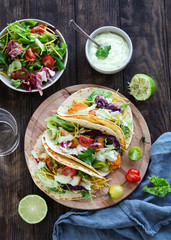 Fish tacos with salad and yogurt sauce on a wooden background