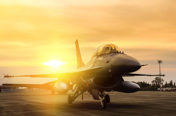 f16 falcon fighter jet parked  on sunset  background