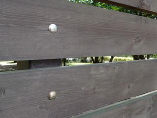 деревянные доски коричневого цвета через которые видно сад