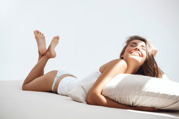 Young beautiful girl lying on bed early in morning.