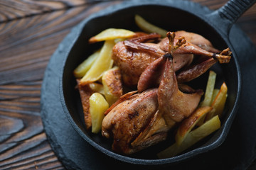 Baked quails with roasted potato in a cast-iron frying pan