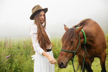 Young woman with brown horse outdoors