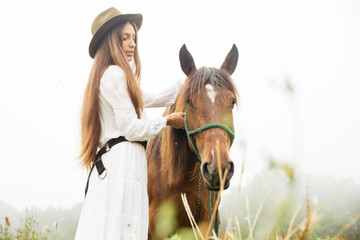 Young woman with horse outdoors