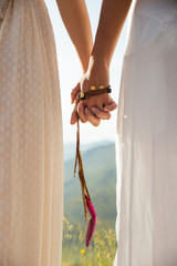 Two girlfriends hand in hand with indian accessory