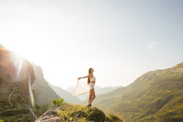 Happy woman with outstretched arms against of beautiful landscape