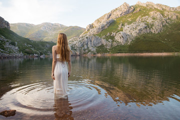 Back view of red-haired woman in dress in mountain lake