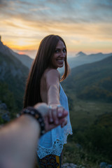 Beautiful brunette woman smiling at camera in mountains.Follow me.