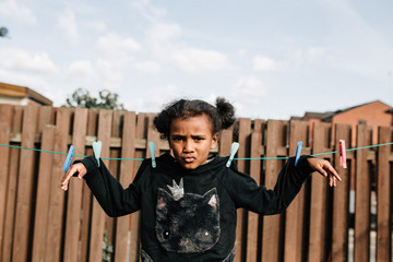 Portrait of little afro-american girl hanging on clothespins