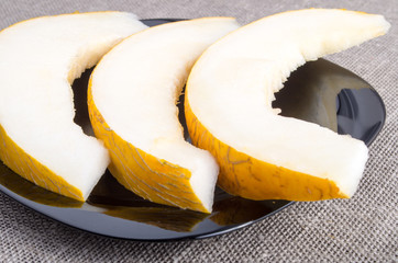 Healthy yellow melon on a black plate
