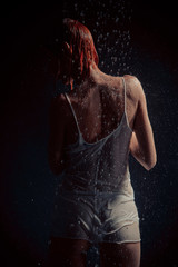Shower. Girl in a white T-shirt standing under a shower.
