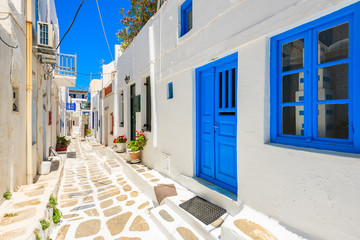 Typical white Greek houses with blue doors and windows on street of beautiful Mykonos town,...