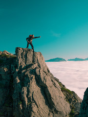 Toned image adult man with backpack stands on the edge of a cliff and screams and shows his hand into the distance against the blue sky and thick clouds floating down