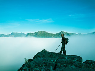Toned image of an adult woman standing on top of a mountain with a backpack and Alpenstocks against mountains in a fog and the blue sky