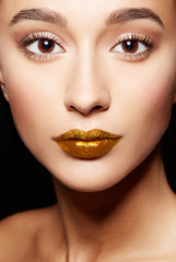 Closeup of beautiful woman face. Gold lip color, golden glitter upper lip and shiny lipgloss. Makeup and cosmetic image.